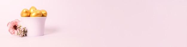 Osterkomposition der goldenen dekorativen eier in einer porzellantasse und einer blume auf einem rosa hintergrund. selektiver fokus, kopierraum.