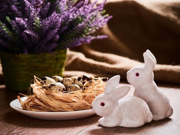 Osterkomposition kaninchen mit eiern auf holztisch, ostereier im nest und frühlingsblumen. draufsicht mit kopierraum