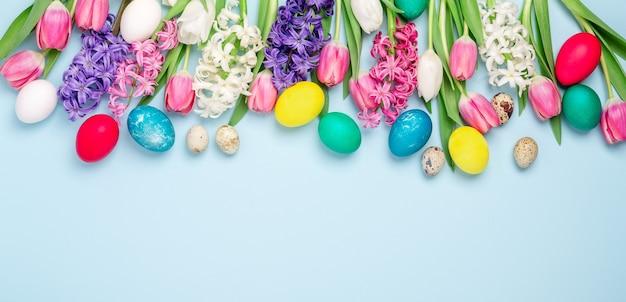 Osterkomposition. mehrfarbige ostereier, tulpen und hyazinthen auf blauem hintergrund. osterkonzept. speicherplatz kopieren - bild