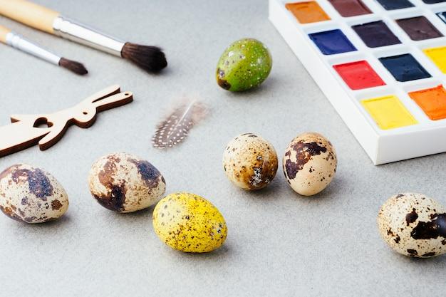 Osterkomposition mit bemalten eiern in einem korb, einem kaninchen und farben auf grauem hintergrund. ostertradition, hintergrund. vorbereitung für die feier von ostern, ein kreatives konzept.