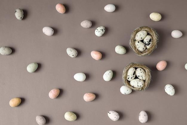 Osterkomposition mit bunten ostereiern im vogelnest auf schokoladenhintergrund