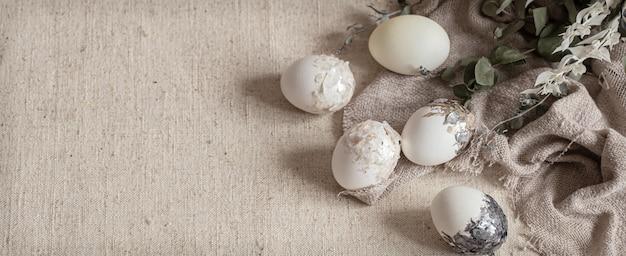 Osterkomposition mit dekorativen eiern auf sackleinen und trockenen zweigen kopieren platz.