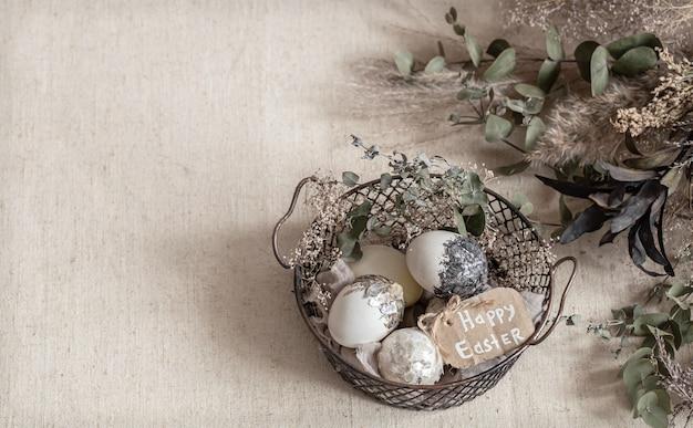 Osterkomposition mit dekorativen eiern in einem korb auf einem strukturierten hellen oberflächenkopierraum.