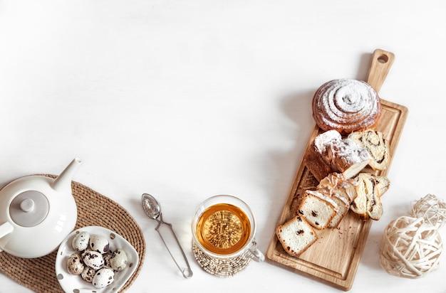 Osterkomposition mit frischem gebäck und einer tasse tee und einer teekanne. feiertags-teeparty-konzept.