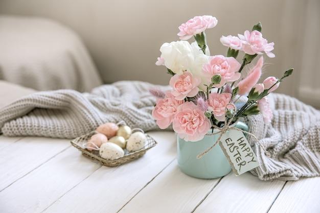 Osterkomposition mit frischen blumen in einer vase, einem gestrickten element und der aufschrift frohe ostern auf der karte.