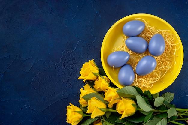 Osterkomposition mit gelben rosen und eiern auf dunkelblauem hintergrund