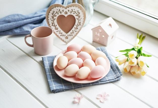 Osterkomposition mit gelben tulpen und rosa eiern