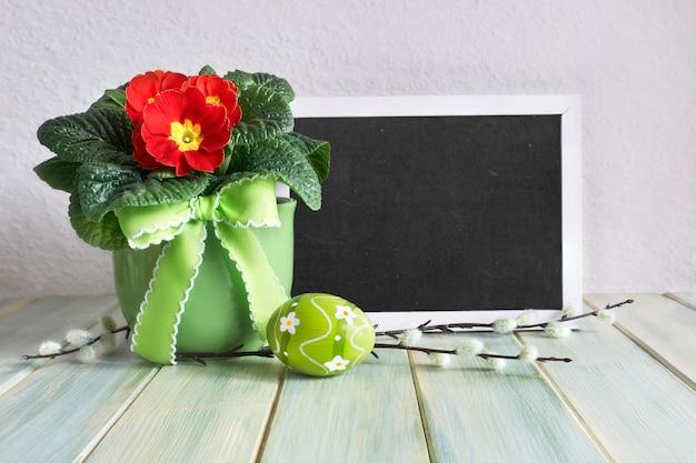 Osterkomposition mit gemalten ostereiern und roter primelentopfblume auf rustikalem holz