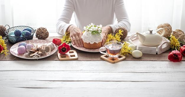 Osterkomposition mit kuchen in weiblichen händen, tee, blumen, eiern und dekordetails. oster-familienferienkonzept.