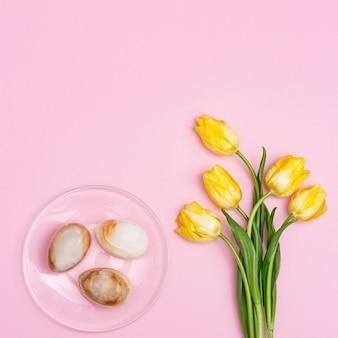 Osterkomposition mit natürlicher tulpenblume und dekorativen eiern aus edelstein-onyx. frühlings-osterferien