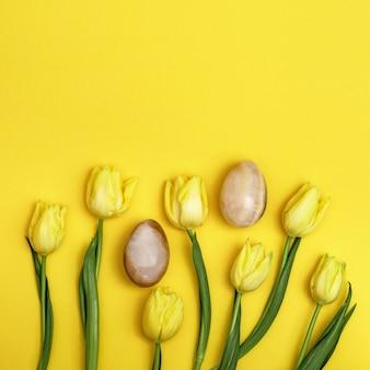 Osterkomposition mit natürlicher tulpenblume und dekorativen eiern aus edelstein-onyx