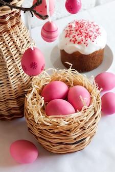 Osterkomposition mit rosa gefärbten eiern im weidenkorb und im osterkuchen