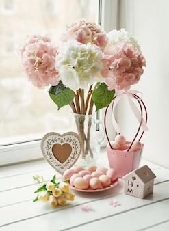 Osterkomposition mit rosa und weißen hortensien in vase, gelben tulpen und rosa eiern