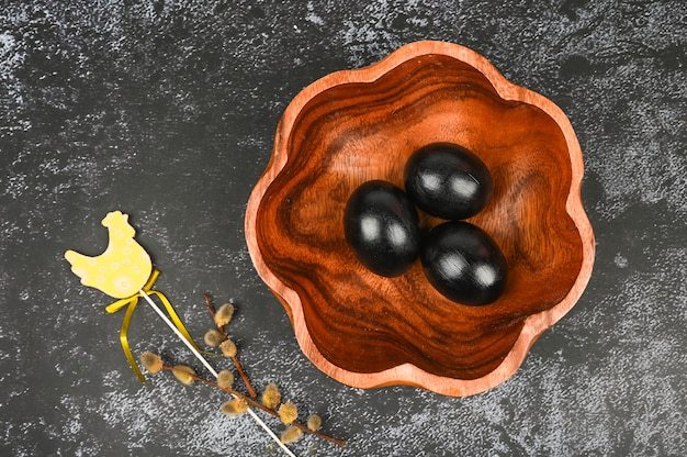 Osterkomposition mit schwarzen eiern, weiden und hölzernen chiken.