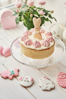 Osterkomposition mit süßem kuchen mit erdbeerglasur, rosa eiern und rosen