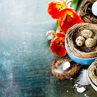 Osterkomposition mit tulpen und nestern