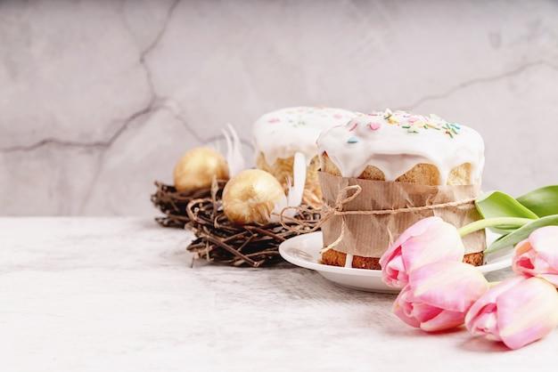 Osterkonzept. glasierte osterkuchen mit tulpen und farbigen eiern vorderansicht