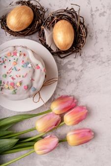 Osterkonzept. glasierter osterkuchen mit tulpen und farbigen eiern draufsicht flach lag