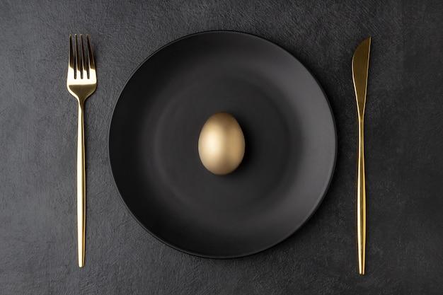 Osterkonzept mit einem goldenen ei auf einem schwarzen teller