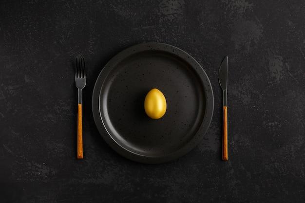 Osterkonzept mit goldenem ei auf einem schwarzen teller über schwarzem schiefer, stein oder betonhintergrund. draufsicht mit kopierraum.