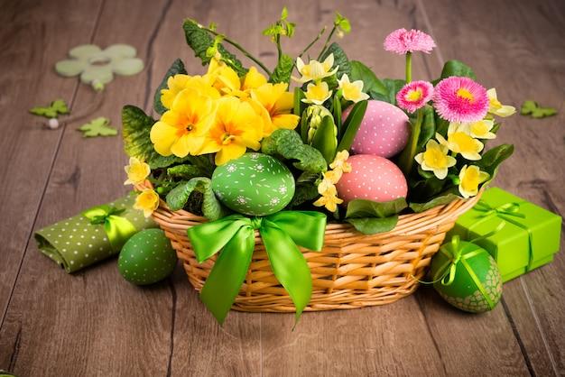 Osterkorb auf holz mit handgemachten dekorationen
