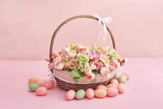 Osterkorb mit blumen und eiern auf rosa hintergrund