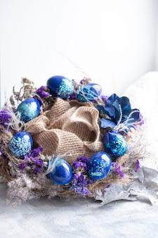 Osterkranz mit blauen eiern mit pailletten am fenster.