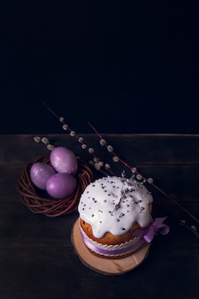 Osterkuchen auf einem, mit lavendel und marshmallows dekorierten und bemalten ostereiern in einem weidennest.