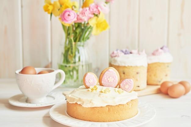 Osterkuchen auf tisch, makronen, eiern und blumenstrauß in vaseaster