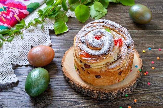 Osterkuchen, bemalte eier, grüne zweige auf einem holztisch. frühlingsferienhintergrund