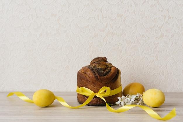 Osterkuchen, gelb bemalte eier und blumen auf einem beigen tisch. frühlingsferienzeit. traditionelle festliche tafel. platz kopieren