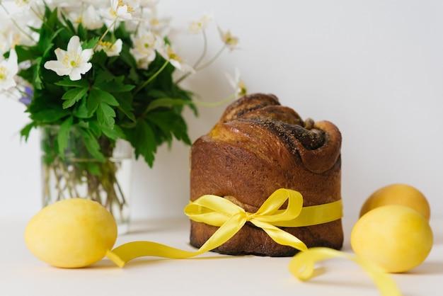 Osterkuchen, gelb bemalte eier und blumen auf einem beigen tisch.