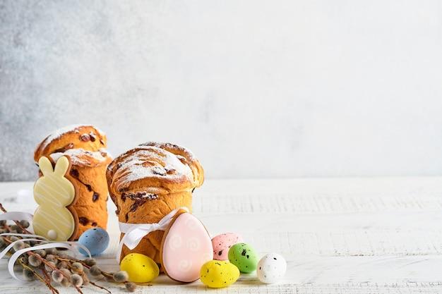Osterkuchen, helle eier, lebkuchen und weidenkätzchenzweige auf einem festlichen ostertisch. grußkarte.