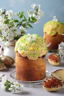 Osterkuchen mit farbiger glasur und dekoration bestreuen und ostereier mit gewürzen und müsli verziert, vertikales format, nahaufnahme