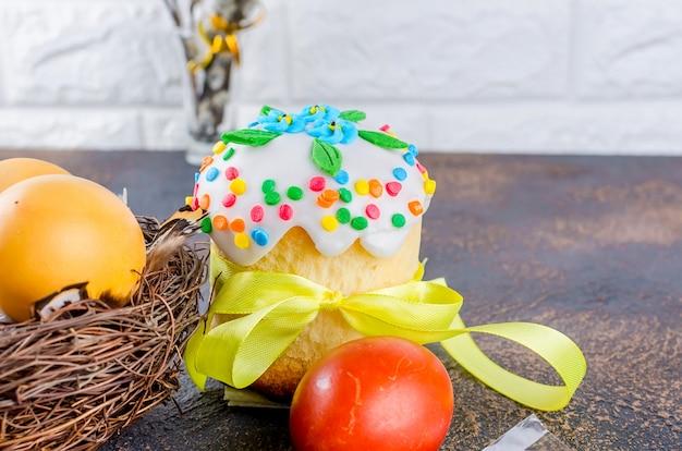 Osterkuchen, rote eier, feiertagsdekorationen und gedeck für ostern