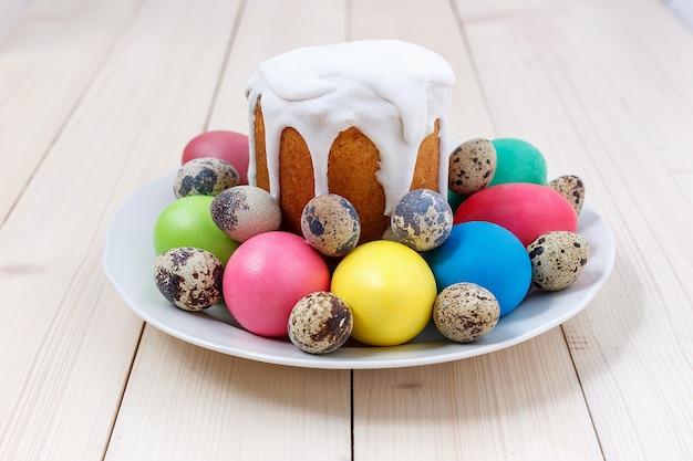 Osterkuchen und bunte eier auf einer platte auf einem holztisch. frohe ostern-konzept