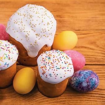 Osterkuchen und osterfarbene eier auf einem holz