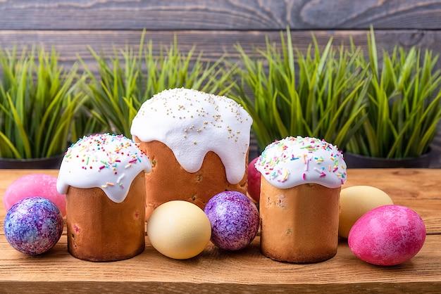 Osterkuchen und osterfarbene eier auf einer holzoberfläche