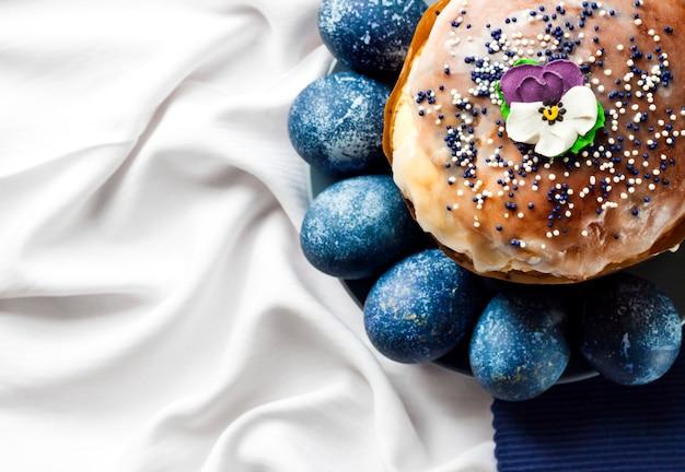 Osterkuchen verziert mit zuckerblume und blau gefärbten eiern auf einem teller auf weißem und blauem stoff