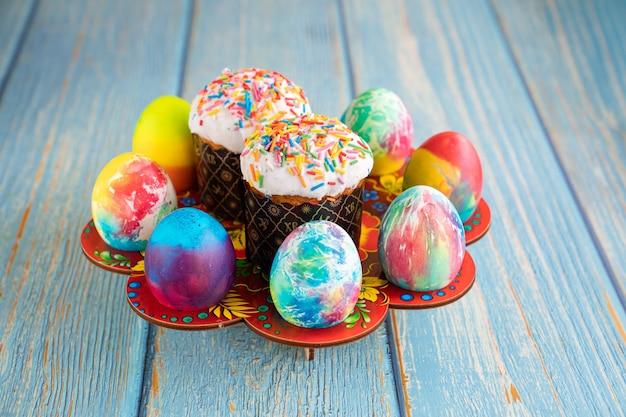 Osterkulich und dekorierte eier. platz für text auf türkisfarbenem holzhintergrund. ein traditioneller festtagsgenuss.