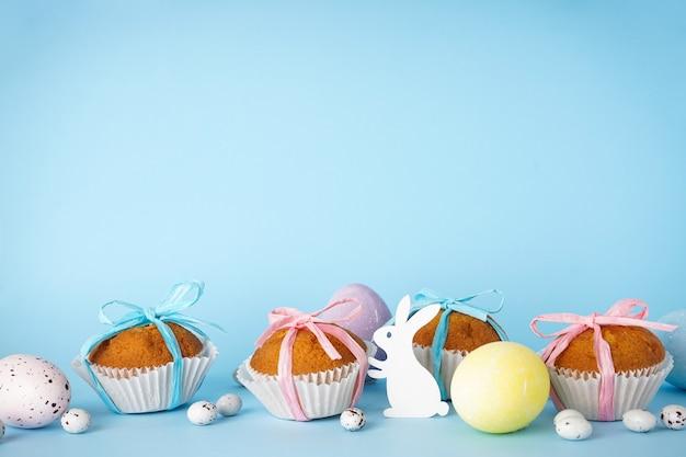 Osterleckereien, bunte cupcakes auf blauem hintergrund, platz für text.