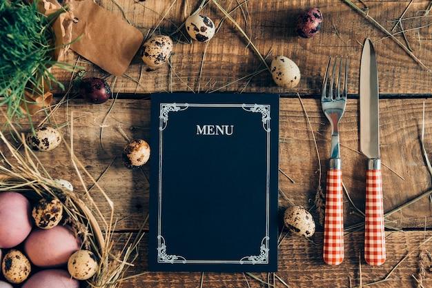 Ostermenü zum abendessen. draufsicht auf ostereier und menütafel mit gabel und messer, die auf rustikalem holztisch mit heu liegen