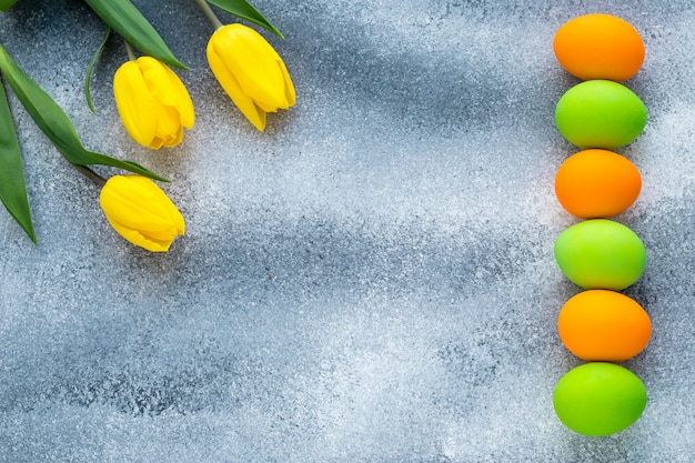 Ostermodell mit textraum. festlicher osterrahmen mit bunten eiern und gelben tulpen auf grauem betonhintergrund.