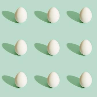 Ostermuster mit weißen eiern auf grünem papier lebensmittelhintergrund osterdruck