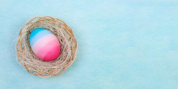 Ostern aquarell ei liegt auf einem sisal in einem weidenkorb auf einem hellblauen hintergrund