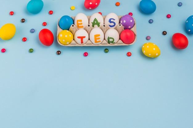 Ostern-aufschrift auf eiern im gestell auf blauer tabelle