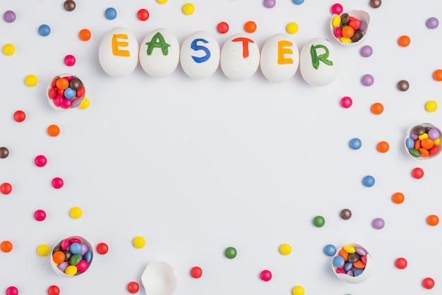 Ostern-aufschrift auf eiern mit süßigkeiten auf weißer tabelle