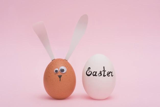 Ostern-aufschrift auf weißem ei mit häschen