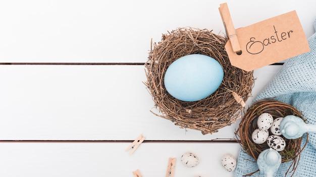 Ostern-aufschrift mit blauem ei im nest
