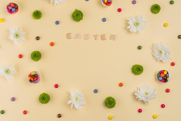 Ostern-aufschrift mit blumen und süßigkeiten auf tabelle
